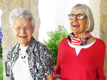 Two residents from Trinity Village, an Immanuel senior living community, wear patriotic apparel and wave small American flags as they welcome American Legion Riders to the community in celebration of veterans.