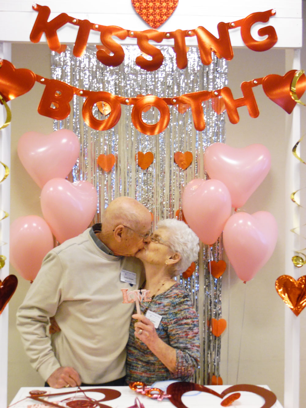 Residents get cozy in the Valentine's Day kissing booth at Pacific Springs Village