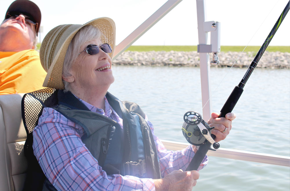 Residents at The Arboretum, a senior living community in Omaha, Nebraska, enjoy a day fishing out on the lake with the non-profit organization Live Well. Go Fish.