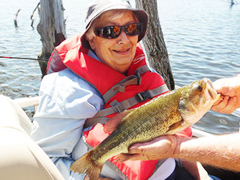 A resident from Trinity Village, an Immanuel community, poses with a fish she caught while out on a pontoon with the organization Live Well. Go Fish.