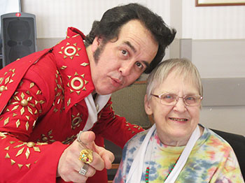 An Elvis impersonator poses with a resident from Immanuel Fontenelle for a photo