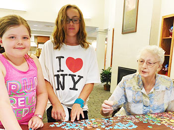 A resident from Clark Jeary, a senior living community in Lincoln, Nebraska, creates cards with kids from Trinity Daycare during one of the community's intergenerational activities.