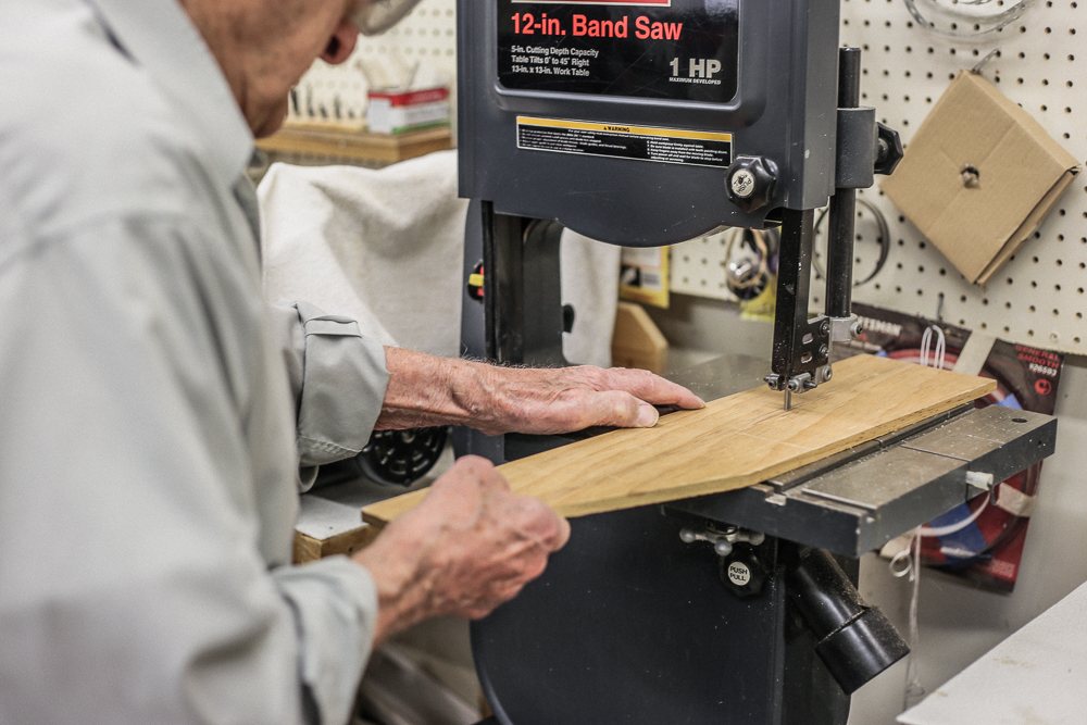 howard uses the band saw in the woodshop to cut through a piece of wood