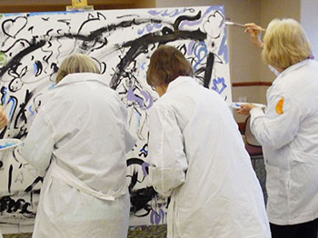 Residents from The Landing senior living community paint a white canvas during one of their life enrichment activities