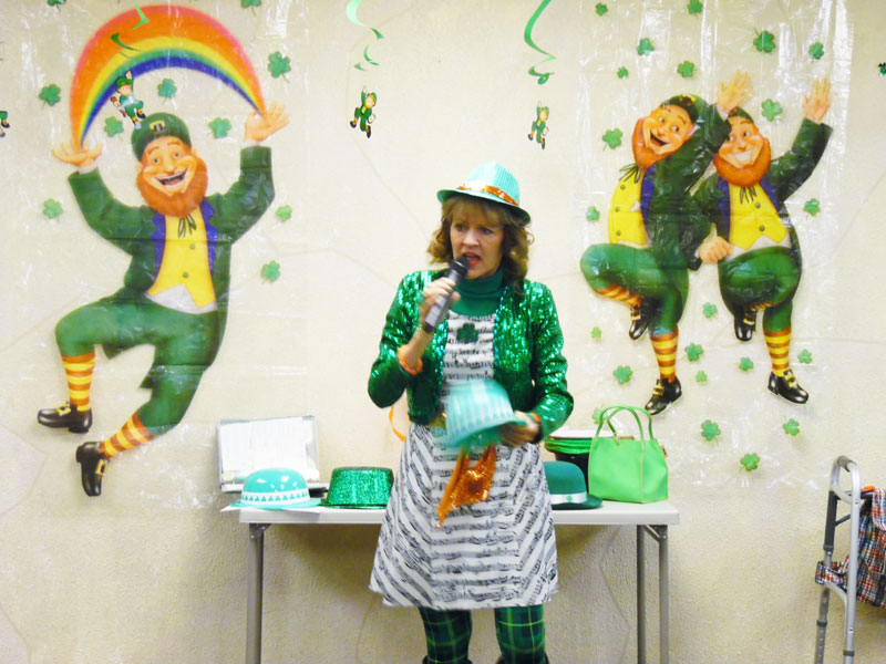 Cynthia, the Queen of Theme, is dressed head to toe in Irish apparel and introduces residents to some Irish tunes