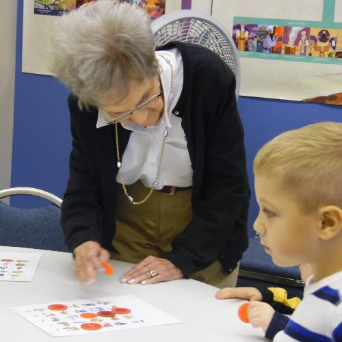 A Resident From Trinity Village Plays Thanksgiving JINGO With Visiting School Children