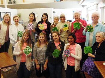a group of trinity village residents and ladies from the american heart association sweetheart leadership program hold up their four leaf clover crafts on saint patricks day