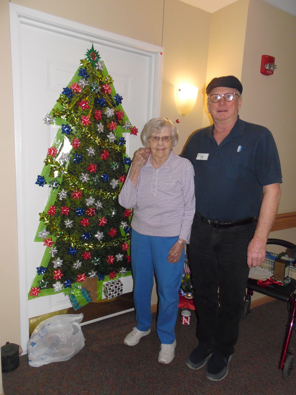 A resident and staff member pose in front of a decorated door at Immanuel Courtyard senior living community